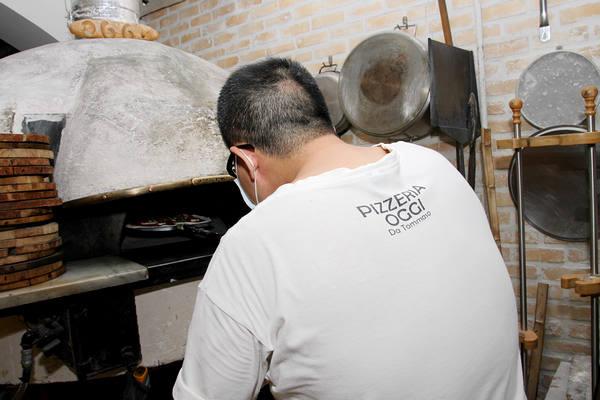 小心翼翼将披萨送进石头窑炉中
